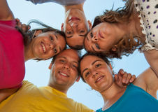 Five friends sharing a hug. Five young people in a circle, sharing a hug, smiling. Captured from low point of view stock photography
