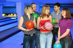 Five friends stand with balls for bowling. And look on each other, focus on girl in center and on right Royalty Free Stock Photography