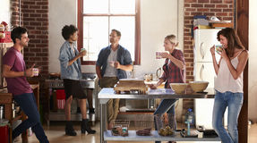 Five friends stand hanging out in kitchen, quarter length royalty free stock photo