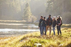 Five friends walking near a lake stop to take in the view Royalty Free Stock Photo