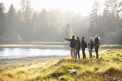Five friends walking near a lake take in view, one points Stock Photography