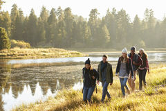 Five friends walking in a row in countryside beside a lake Stock Photo