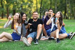 Five friends women and men inflate soap bubble outdoors Royalty Free Stock Images