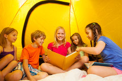 Five funny kids read book in a tent Stock Images