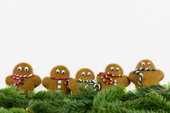 Five gingerbread men with fir branches Royalty Free Stock Photo