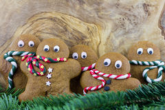 Five gingerbread men and pine branches Royalty Free Stock Photo