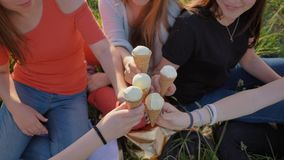 Five girls join hands clinking ice cream. Hands close-up. stock footage