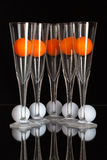 Five glasses of champagne, white and orange golf balls Royalty Free Stock Photography