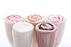 Five glasses of various milkshakes chocolate, strawberry and vanilla isolated on white background Royalty Free Stock Image