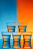 Five glasses with water over blue and orange background. Stock Images