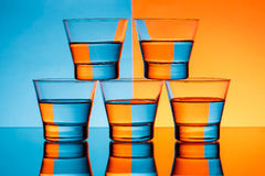 Five glasses with water over blue and orange background. Stock Photography