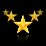 Five gold stars in the shape of wedge on black. Five gold stars on black background - the first one in focus, the others blurry Royalty Free Stock Photo