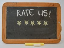 Five golden stars rate us. A blackboard with the text  rate us! With five golden stars to vote for quality Stock Photography