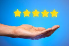 Five golden yellow stars out of five. Man holds star on the palm of his hand, puts rating, reviews stock photo