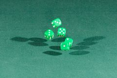 Five green dices falling on a green table. Five green dices falling on a isolated green table stock photo