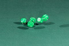 Five green dices falling on a green table. Five green dices falling on a isolated green table royalty free stock images