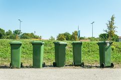Five green plastic industrial garbage cans with junk and litter on the street in the city waiting for dumper truck to collect them.  royalty free stock photos
