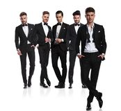 Five groomsmen with leader with undone collar in front. Five groomsmen in black tuxedoes with leader with undone collar standing in front cross-legged, on white stock photography