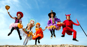 Five Halloween Children Jumping at the Blue Sky. Stock Photo
