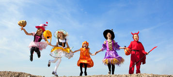 Five Halloween Children Jumping at the Blue Sky. Royalty Free Stock Photography
