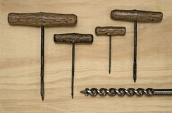 Five Hand Drills. Five Vintage Hand drills of various sizes on a wooden background Stock Image