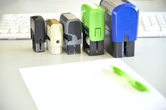 Five handle automatic stamps, sheet of paper and pen on a desk stock image