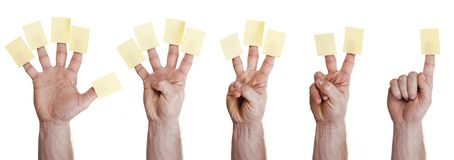 Five hands holding post it on finger Stock Image