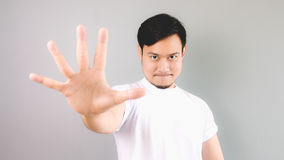 Five hands signs with confident face. An asian man with white t-shirt and grey background royalty free stock images