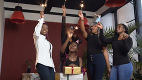 Five happy african girl celebrating with bengal lights, dancing during birthday party. Dolly shot. stock footage