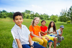 Five happy friends sit on chairs in row outdoors Stock Photography