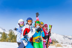 Five happy friends with snowboards and skis Royalty Free Stock Photo