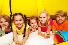 Five happy kids laying in tent and smile Royalty Free Stock Photo