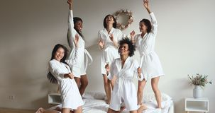 Happy diverse girls friends wear dressing gowns dancing on bed