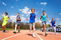 Five happy teenage kids running on the stadium. Group of five happy teenage kids in sportswear, running on the stadium on sunny day Stock Image