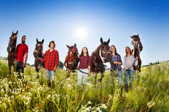 Five happy young people with their horses in field Stock Images
