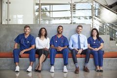 Five healthcare workers sitting in hospital, full length royalty free stock image
