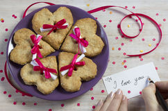 Five heart shape cookies on purple plate. Tasty surprise in the message for lovers Stock Photo