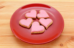 Five heart-shaped iced cookies on a red plate Royalty Free Stock Photos