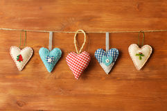 Five hearts made of cloth on wood background Stock Image
