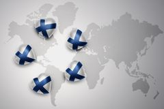 Five hearts with national flag of finland on a world map background. Royalty Free Stock Photo