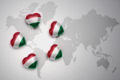 Five hearts with national flag of hungary on a world map background. Stock Photos