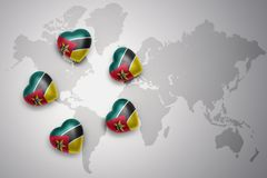 Five hearts with national flag of mozambique on a world map background. Concept.3D illustration Royalty Free Stock Photos