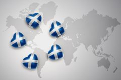 Five hearts with national flag of scotland on a world map background. Stock Photo
