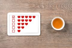 Five hearts rating in digital tablet. Tea cup, office table stock photography