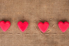 Five  hearts on sackcloth Royalty Free Stock Images