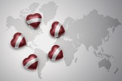 Free Five Hearts With National Flag Of Latvia On A World Map Background. Royalty Free Stock Photography - 104278997