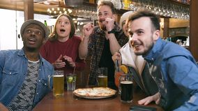 Five hipster friends drinking beer, cocktail while cheering for sports game in pub, bar, stock footage