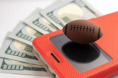 The ball for rugby or American football lies on the screen of the smartphone in a red case. Five hundred dollars usa background. Five hundred dollars usa stock images