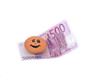 Five hundred euros and smiling chicken egg. Money five hundred euros and brown chicken egg painted on it with a smile on white won the Royalty Free Stock Image
