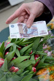 Five hundred rubles in a hand of the elderly woman against the background of tulips Stock Photography